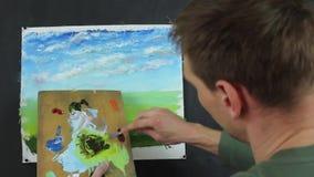Konstnär som arbetar på en målning Olje- målning för konstnärmålarfärg på kanfas arkivfilmer