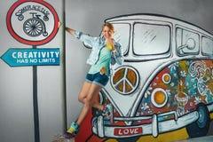 Konstnär som dricker jucemålning mot hippiekortkortskåpbilen arkivfoton