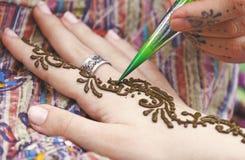 Konstnär som målar den traditionella indiska hennatatueringen på kvinnahanden royaltyfria bilder