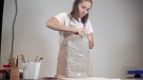 Konstnär som packar upp ett stort stycke av en lera i hennes studio stock video