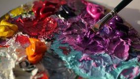 Konstnärblandningar på politrilarosa färger och svartfärger med en borste, 4k arkivfilmer