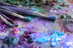konstnärborstar och olje- målarfärger på träpaletten Royaltyfri Bild