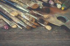 Konstnärborstar och rör med målarfärg på paletten Arkivfoto