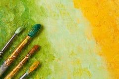 Konstnärborstar på konstnärlig bakgrund Royaltyfria Bilder
