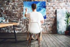 Konstnären är målarfärg per olje- målning i konststudio, medan sitta på en stol framme av en kanfas Målareteckningsprocess i vind royaltyfri bild