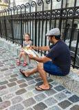 Konstnären arbetar på ståenden av den lilla flickan vid järnstaketet av Sacre Coeur, Paris, Frankrike Royaltyfria Bilder