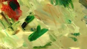 Konstnären blandar olje- målarfärg för olika färger på paletten arkivfilmer