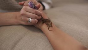 Konstnären drar mehndimodeller på kvinnahänder, närbild arkivfilmer