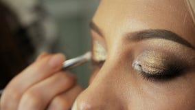 Konstnären för skönhetsalongmakeup målar skuggorna på ögonen med en borsteblondinkvinna arkivfilmer