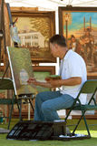 Konstnären fungerar på målning på den utomhus- festivalen royaltyfria bilder
