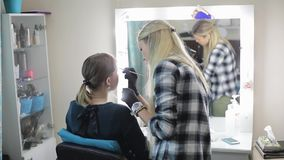 konstnären gör model övre Ung blondin Ögonbrynen för teckning för sminkkonstnär till en nätt flicka med en yrkesmässig borste arkivfilmer