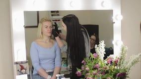 konstnären gör model övre 15 woman young Ögonbrynen för teckning för sminkkonstnär till en nätt flicka med en yrkesmässig borste  lager videofilmer