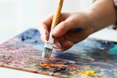 konstnären målar en bild av borsten för olje- målarfärg i hand med paletten Arkivfoto