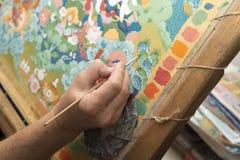 Konstnären målar en buddistisk symbol Royaltyfria Foton
