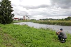 Konstn?ren m?lar ett landskap med en sikt av kyrkan av Elijah profeten royaltyfria foton