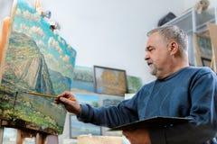 Konstnären målar olje- målning med en borste och en palett Arkivfoto