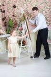 Konstnären målar ståenden av den gulliga lilla flickan Royaltyfri Bild