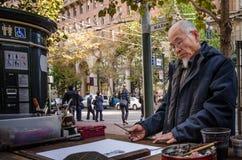Konstnären målar utomhus på marknadsgatan i San Francisco Fotografering för Bildbyråer