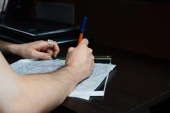 Konstnären omringar pennan skissar av en tatuering på skrivbordet Arkivfoto