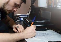 Konstnären omringar pennan skissar av en tatuering på skrivbordet royaltyfri fotografi