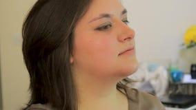 Konstnären riktar kvinnas ögon- och applyseyeliner med borsten lager videofilmer