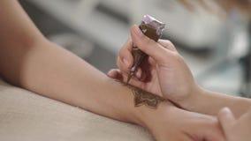 Konstnären skapar dekorativa designer på händer för en kvinna, genom att använda hennadeg lager videofilmer