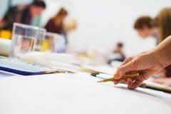 Konstnären skissar en blyertspenna i en skola av målning som förbereder en tom kanfas för skapelsen av en målning royaltyfri foto