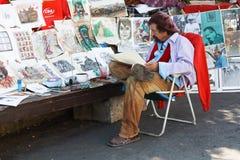 Konstnären som förläggas i stadfyrkanten och, drar karikatyrer av folk Arkivfoton