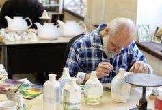 Konstnären som målar keramiska flaskor Arkivbild