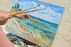 Konstnärens hand som rymmer en borste som målar bilden Arkivfoto