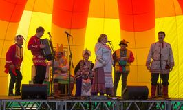 Konstnärer av den folk helheten av jonglörer och clowner utför shower på etappen i maslenitsadag Royaltyfri Foto
