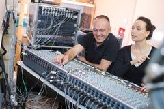 Konstnärer som producerar musik i deras, returnerar den solida studion arkivfoto