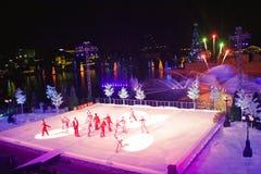 Konstnärgruppen som åker skridskor på jul, visar på is på färgrik bakgrund med fyrverkerier i internationellt drevområde arkivbild