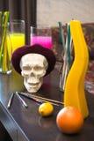 Konstnärlig atmosfär: vas med kulört vatten, idérikt lynne, skalle i basker Fotografering för Bildbyråer