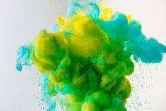 konstnärlig bakgrund med flödande turkos, guling och gräsplan målar i vatten som isoleras på grå färger royaltyfria bilder