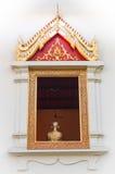 Konstnärlig bild av guld- buddha inom ett fönster Royaltyfri Fotografi