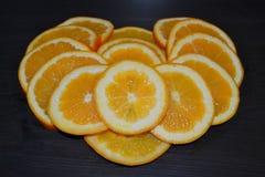 Konstnärlig sammansättning av skivor av mogna apelsiner som poseras i en form av en hjärta på träbakgrund arkivbild