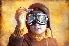 Konstnärlig stående av barnet med den tidigare flygdräkten arkivfoton