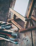 Konstnärlig utrustning: kanfas på staffli-, palett- och målarfärgborstar Royaltyfri Fotografi