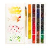 Konstnärlig vattenfärgmålarfärg och borste i plast- ask med paletten Arkivfoton