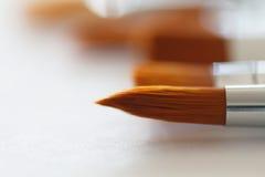 Konstnärliga borstar i makroen av konstnären på en vit tabell Arkivfoto