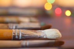 Konstnärliga borstar i seminariet Borstar konstnären på en abstrakt suddig bakgrund i studion för konstnärer Arkivbild