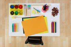 Konstnärliga hjälpmedel på den vita lilla tabellen med liten stol för barn Arkivfoton
