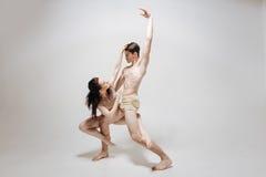 Konstnärliga unga dansare som utför i den vita kulöra studion Fotografering för Bildbyråer