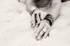 Konstnärligt foto av kvinnlighänder med smycken som täckas med sandkorn royaltyfri foto