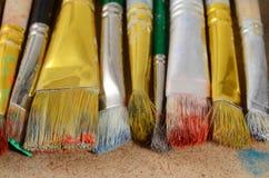 Konstnärs skrivbord med gamla smutsiga färgglade borstar, idérik bakgrund Arkivbild