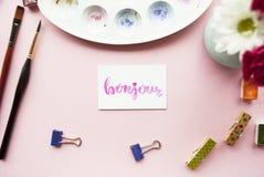 Konstnärworkspace Bonjour som är skriftlig i kalligrafistil, palett, borste, stift, bukett av blommor på en rosa bakgrund Lekmann Arkivfoto