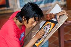konstnären skapar kalachakramandalamålningen Arkivfoton