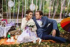 Konstnärliga par i brölloplandskap brudappeller Arkivbild
