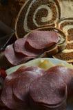 Konstruieren des Salami-und Käse-Sandwiches auf gemarmortem Rye-Brot vor Laib Lizenzfreie Stockfotos
